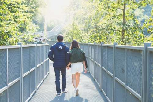 Two young adults walking holding hands